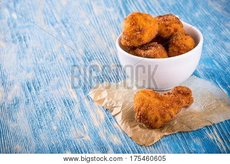 Few Pieces Of Fried Cauliflower On Blue Wooden Board And White Cup