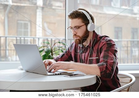 Image of concentrated bearded young man student sitting in cafe while using laptop computer and listening music. Looking at laptop.