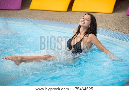 Young Smiling Woman In A Black Swimsuit In A Swimming Pool Enjoying In Jacuzzi