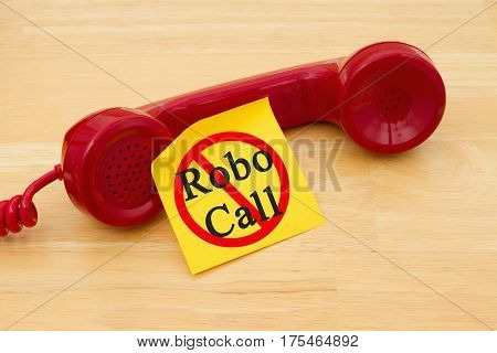 Stop getting a call from a Robocall Retro red phone handset with a yellow sticky note and text Robocall with not icon