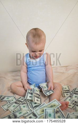 Cute little boy is counting money, hundreds of dollars.