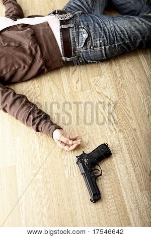 crime scene, dead body on floor and pistol