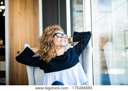 Business woman relaxing working at office desk laid back resting on chair with hands behind head