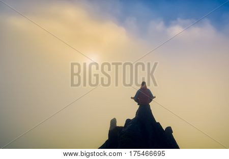 Human Meditating On The Top Of A Mountain