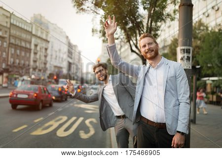Business men hailing a cab in busy city after work