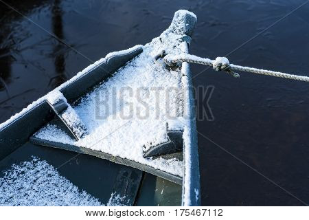 Part of green punter boat in winter with snow and rope and ice on the water.
