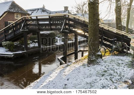 Giethoorn The Netherlands - January 18 2016: Winterlandscape with canal farmhouse bicycle and bridge in the typical dutch village of Giethoorn in the province of Overijssel in the Netherlands.