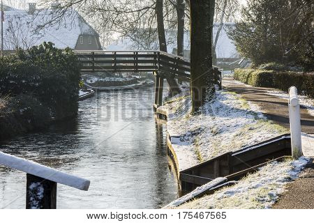 Giethoorn The Netherlands - January 18 2016: Winterlandscape with canal farmhouse and bridge in the typical dutch village of Giethoorn in the province of Overijssel in the Netherlands.
