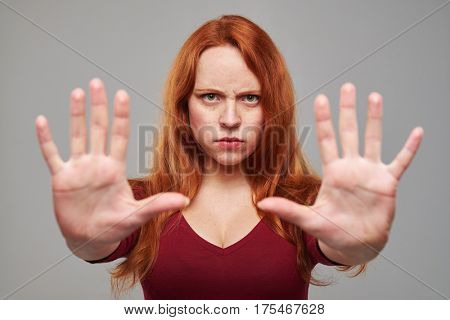 Close-up shot of young woman with auburn hair gesturing stop sign with two hands. Female isolated over gray background