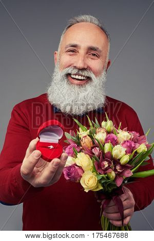 Close-up shot of broadly smiling mature man who is holding a gift box with wedding ring and a bunch of flowers isolated over gray background