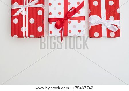 Top view of three big dotted gift box with ribbons and bow ties. Isolated over flat layout with copy space