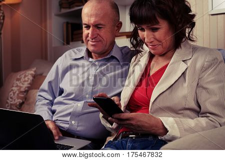 A mid shot of two elderly smiling spouses playing with their devices, sitting on the umber sofa. Booksettle behind them