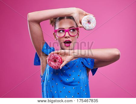 Close-up of surprised woman in lovely bright outfit with doughnut. Joyous trendy young girl giving ok gesture isolated over pink background