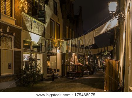 Deventer The Netherlands - December 17 2016: Menstraat (street) in Deventer during Christmas time in the evening with christmas lights and lanterns during Dickens Festival.