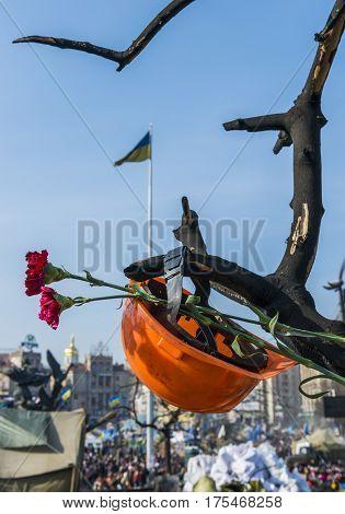 Kiev Ukraine - February 26 2014: Helmet on dead tree in Kiev on Maidan Square during the revolution in the Ukraine.