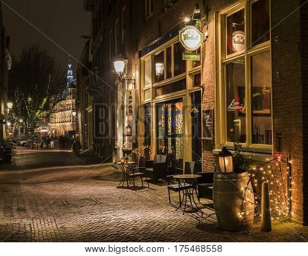 Deventer The Netherlands - December 17 2016: Tapas restaurant in the Polstraat (street) in Deventer during Christmas time in the evening with christmas lights lanterns and a illuminated tower.