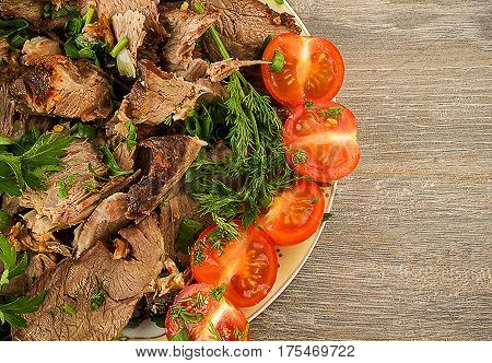Sliced lamb with tomato and greens on a plate