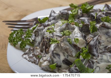 Romanian food - mushrooms with sour cream and parsley on plate with fork