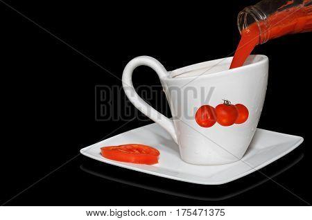 Freshly prepared tomato juice poured into a gravy boat. Black background.