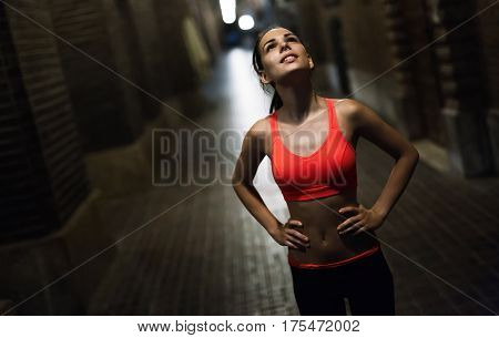 Determined Female Jogger Running In City At Night