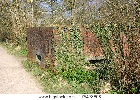 World war two brick pill box with concrete loopholes. Surrounded by trees and part overgrown by ivy. Footpath to one side.