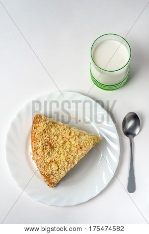 Sweet and delicate cake on a white plate on a table on a light background selective focus. From above. A piece of layered cake is covered with crumbs next to the dessert is a metal vintage spoon and a glass of white yogurt