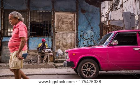 Havana, Cuba on December 23, 2015: A man walks down a street in Centro Habana with his shirt matching the color of a pink oldtimer