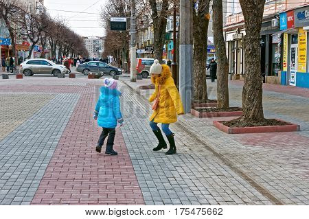 KHMELNYTSKY UKRAINE - FEBRUARY 25 2017: Schoolgirl and her mother are walking and dancing in cool weather on paved street in the downtown of Khmelnytsky Ukraine