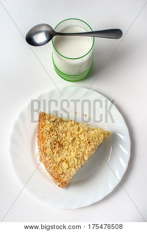 Rustic tender cake on a white plate on a table on a light background selective focus. From above. A layered cake is covered with crumbs next to the dessert is a metal vintage spoon and a glass of white yogurt