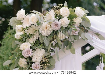 Beautiful wedding archway. Arch decorated with biege cloth and flowers, closeup