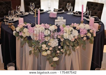 Wedding guest tables, decorated with bouquet and settings and candlesticks, closeup