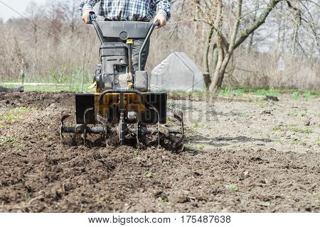 Tractor cultivating field at spring loosens soil by petrol cultivator close-up. Farmer working in the garden with garden tiller.