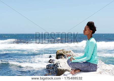 Side portrait of young beautiful woman in yoga pose at the beach