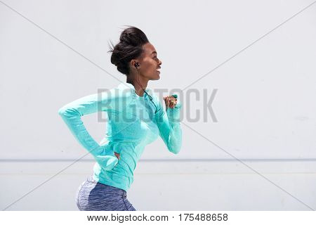 Young Black Woman Running Outside With Earphones