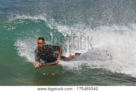 Waikiki Beach, Hawaii, USA -- August 2, 2016: Boogie board surfer catch a wave off Waikiki Beach Hawaii USA