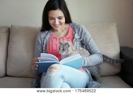 Young woman sitting on sofa with cat and reading book