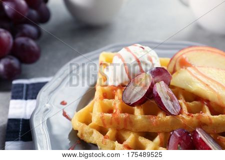 Tasty waffles with delicious fruits, ice-cream and syrup on grey plate, close up