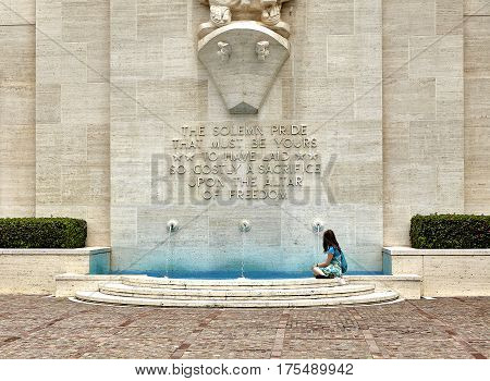 Hawaii, USA -- August 7, 2016: An unidentified woman sits near the fountain monument at National Memorial Cemetery of the Pacific on the island of Oahu, in Hawaii.