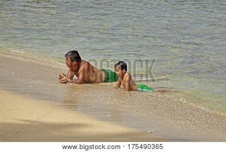 Waikiki Beach, Hawaii, USA -- August 2, 2016: A man and child relax on the beach at Waikiki