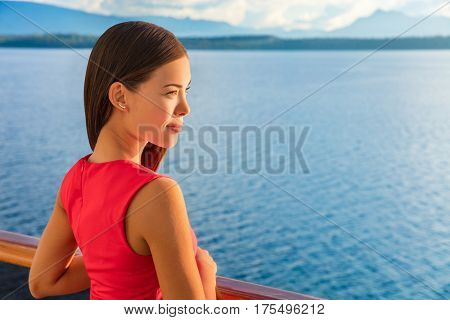 Woman enjoying view of ocean horizon from luxury cruise balcony. Serene ship passenger relaxing outside on suite deck. European travel summer vacation destination.