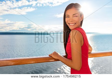 Happy cruise ship passenger outside on suite balcony enjoying luxury view of ocean in travel destination during summer. Beautiful Asian woman.