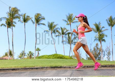 Healthy woman runner jogging on city sidewalk. Happy Fitness girl athlete working out living an active lifestyle training cardio in the morning running in pink sportswear, cap and shoes. Full body.