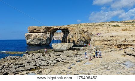 Dwejra, Malta - September 26, 2013. View of the Azure Window in Malta, from a distance, with people. The thrilling coastline of Dwejra, in Gozo, features some astoundingly beautiful rock formations that have been sculpted by the wind and sea.