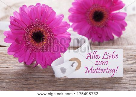 Label With German Text Alles Liebe Zum Muttertag Means Happy Mothers Day. Pink Spring Gerbera Blossom. Vintage, Rutic Or Aged Wooden Background. Card For Spring Greetings.