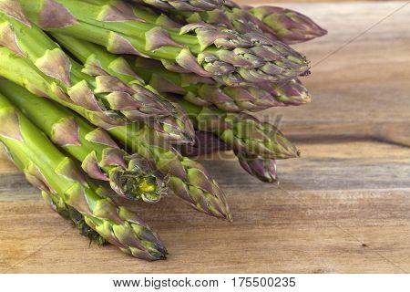 Fresh green asparagus on brown background. Shot in Studio.