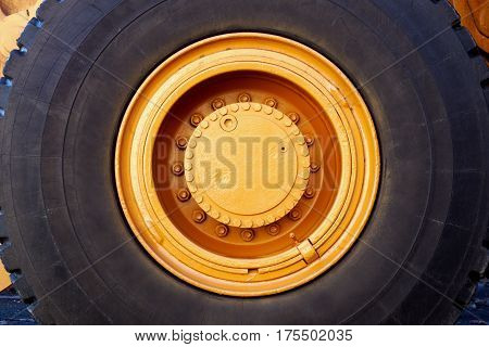 yellow big wheel excavator painted black rubber tire