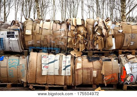 Basingstoke UK - March 6th 2017: Huge piles of cardboard on pallets waiting to be recycled with trees in background