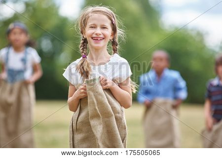 Girl with braided hair at sack race laughing and having fun