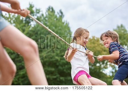 Boy and girl pulling a rope and playing tug of war at the park