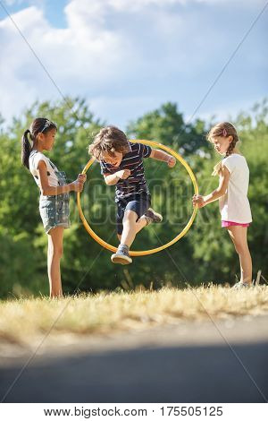 Boy plays at the park and jumps through hula hoop